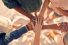young-men-women-showing-unity-group-group-friends-putting-their-hands-together-beach-68053472